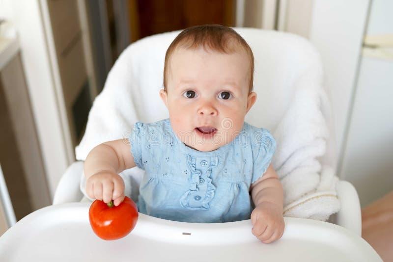 咬住在可口新鲜的蕃茄的愉快的可爱宝贝女孩 孩子的新鲜的健康食品 免版税库存照片