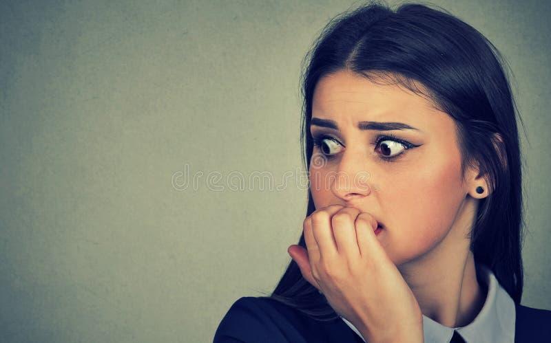 咬住她指甲盖热衷的犹豫的紧张的妇女急切 免版税图库摄影