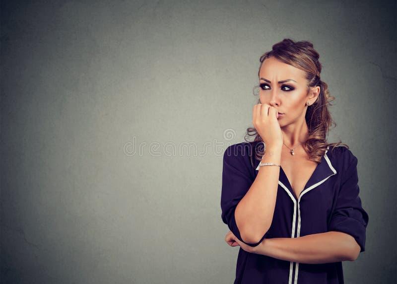 咬住她的指甲盖的出神的急切妇女看对边 免版税库存图片