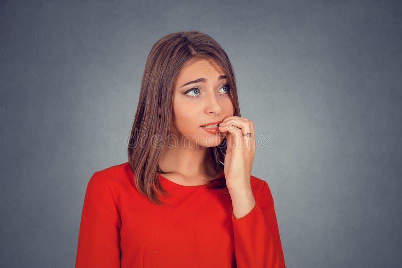 咬住她的指甲盖的紧张的看的妇女热衷某事 免版税库存照片