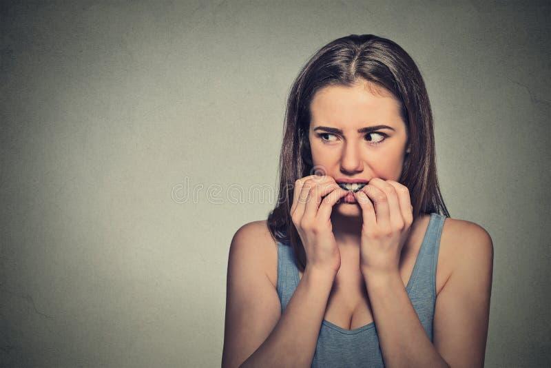 咬住她的指甲盖的缺乏信心的犹豫的紧张的妇女 免版税库存照片