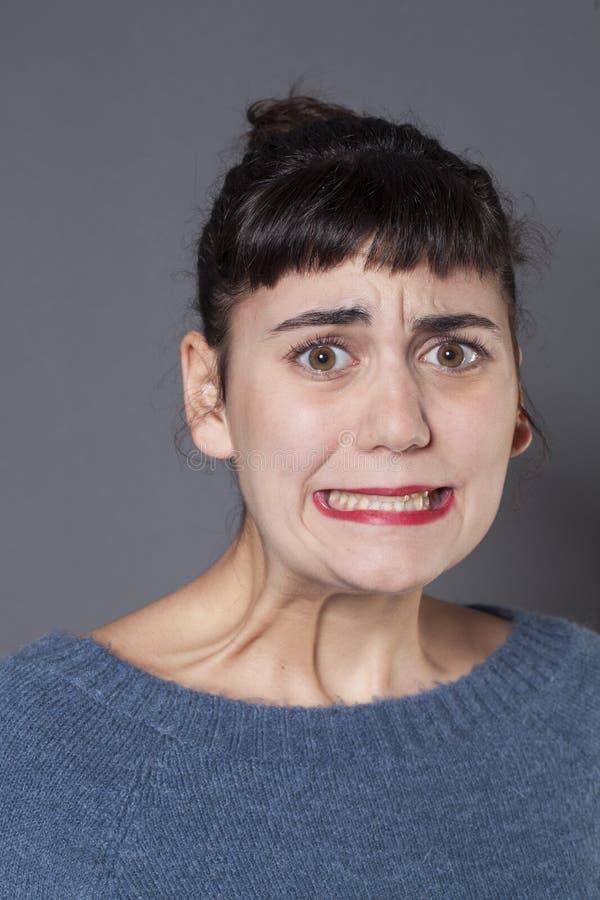 咬住她的牙的害怕的年轻深色的女孩 库存照片