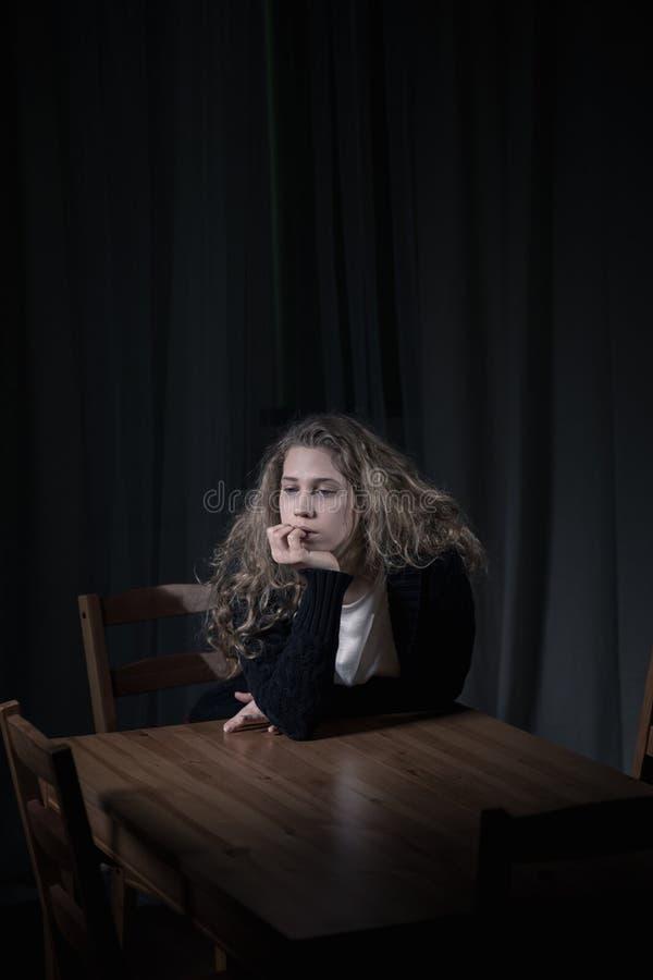 咬住她的钉子的孤独的妇女 库存图片