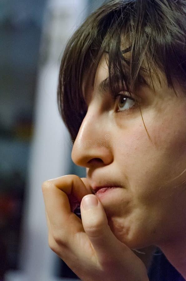 咬住指甲盖的年轻女人 库存照片