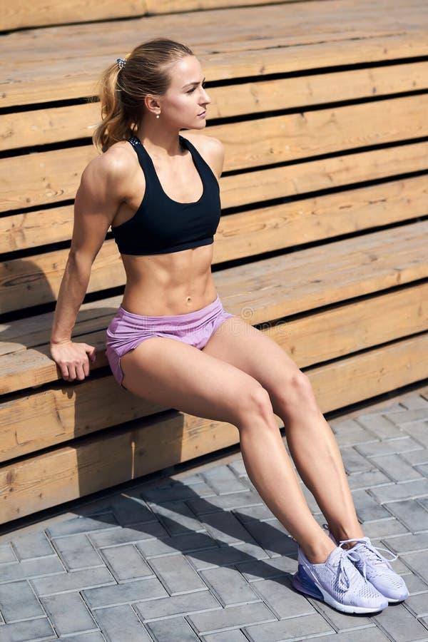 咬嚼abdominals的亭亭玉立的肌肉女孩 图库摄影