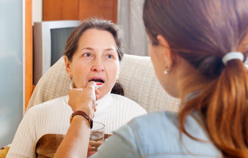 给咳嗽糖浆的妇女母亲 图库摄影