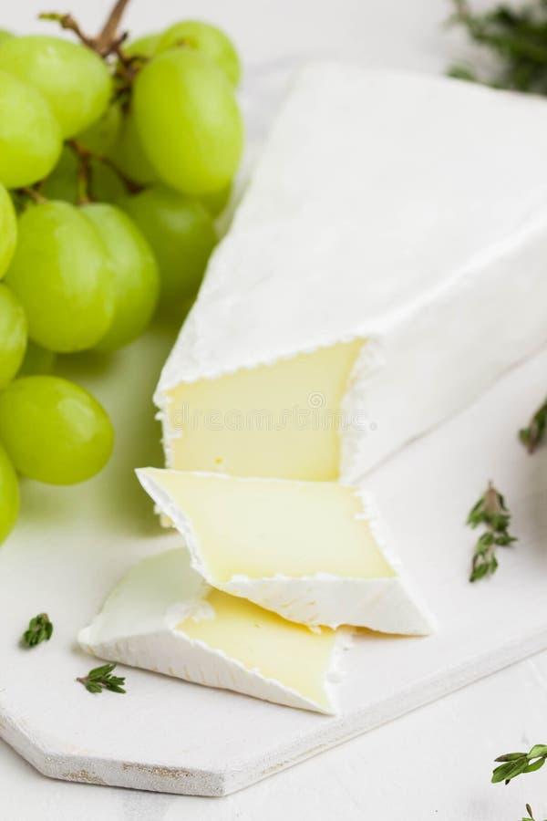 咸味干乳酪乳酪,软制乳酪用绿色葡萄,麝香草在船上 库存图片