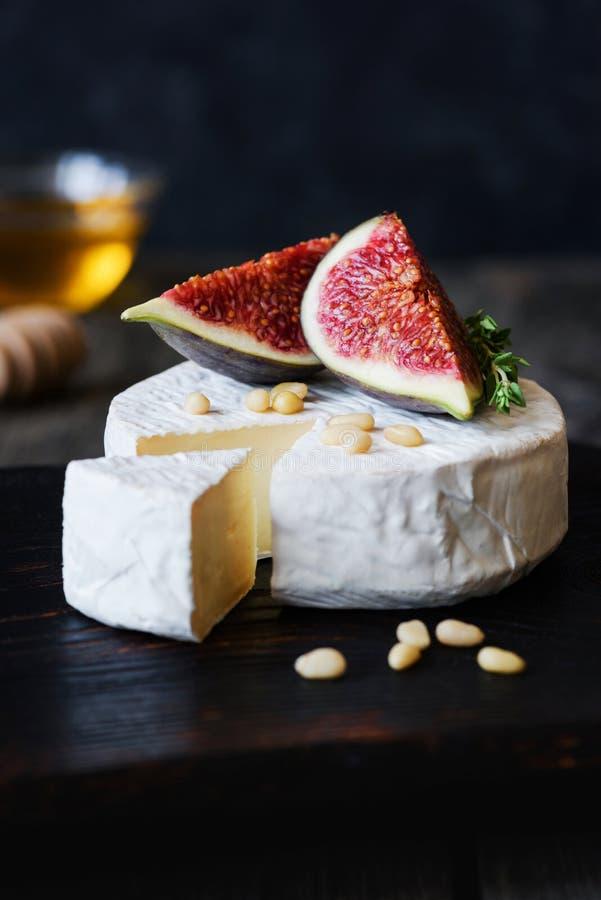 咸味干乳酪或软制乳酪乳酪用无花果、蜂蜜和松果 库存图片