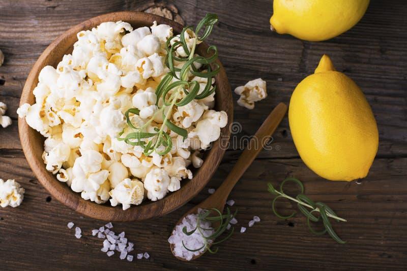 咸嘎吱咬嚼的新鲜的自创玉米花调味与柠檬皮和迷迭香在简单的背景的一个木碗闻 免版税库存照片