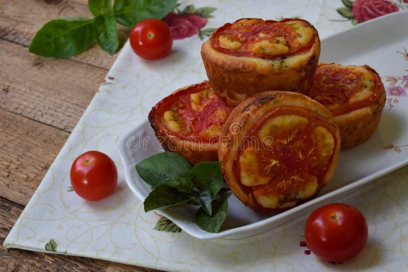 咸快餐 自创松饼用乳酪、蕃茄和蓬蒿在木背景 美味酥皮点心 免版税图库摄影