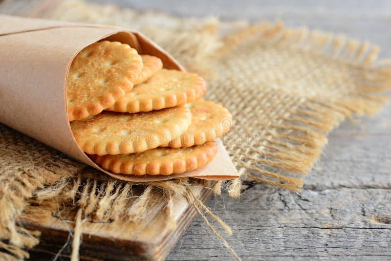 咸稀薄的薄脆饼干在一张包装纸和在麻袋布 葡萄酒木背景 鲜美酥脆薄脆饼干快餐想法 免版税库存图片