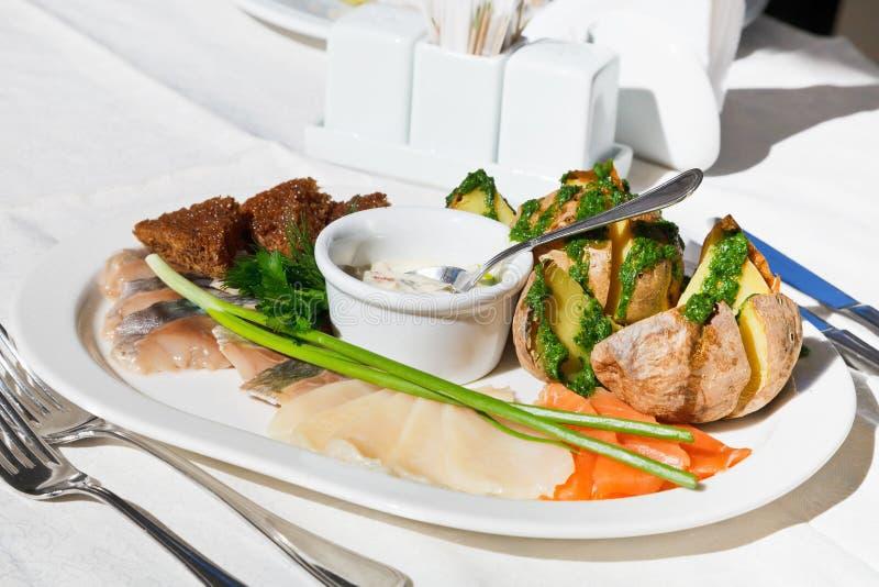 咸鱼用在白色板材的被烘烤的土豆 免版税库存照片
