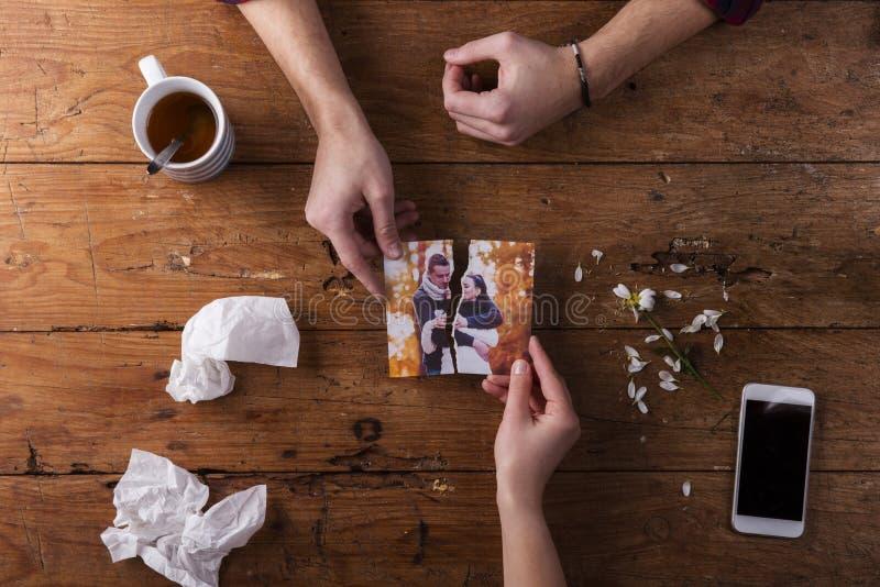 哀伤供以人员,拿着浪漫夫妇的被撕毁的图片妇女手 免版税库存图片