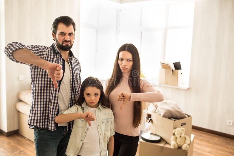 哀伤和不满意的家庭在屋子里站立 他们穿上象房子的` t他们买 人们是显示他们 库存照片