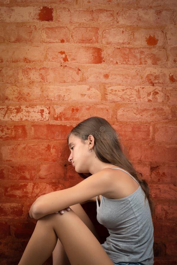 哀伤和孤独的十几岁的女孩坐地板 免版税库存照片