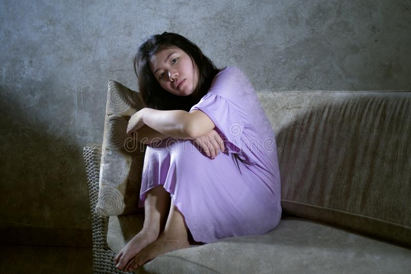 哀伤和沮丧的亚裔中国妇女哭泣的单独绝望和担心在痛苦遭受的消沉和忧虑问题感觉 库存照片