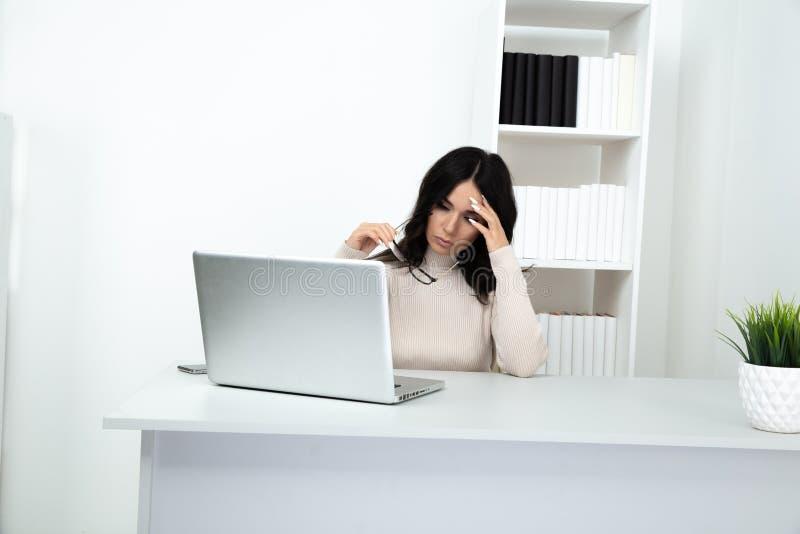 哀伤和被注重的妇女在坐在桌上和运作直到晚的办公室 库存照片