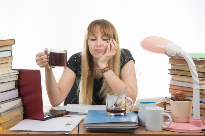哀伤女学生和困读他的在手中坐与一杯咖啡的论文项目 免版税图库摄影