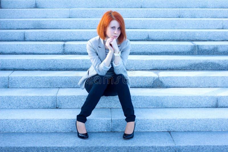 哀伤妇女坐外部和等待某人 免版税库存图片