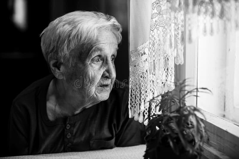 哀伤年长哀伤的妇女看起来窗口 免版税库存照片