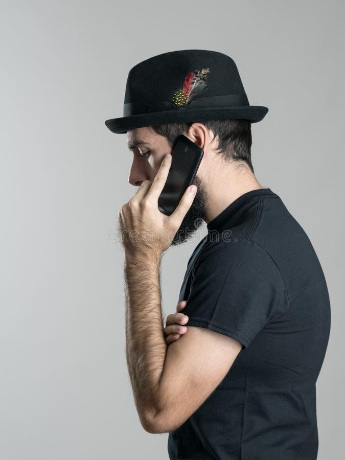 哀伤的串珠的行家侧视图谈话在看的手机下来 库存照片