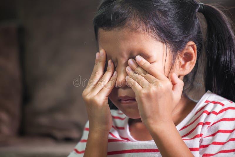 哀伤的亚裔儿童女孩是哭泣和摩擦她的眼睛 库存照片