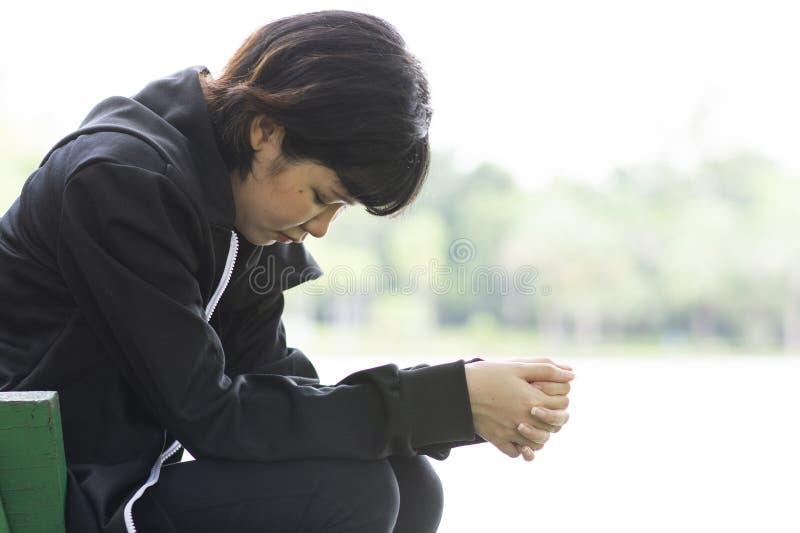 哀伤的亚裔妇女单独坐长凳在湖附近在庭院里 库存照片