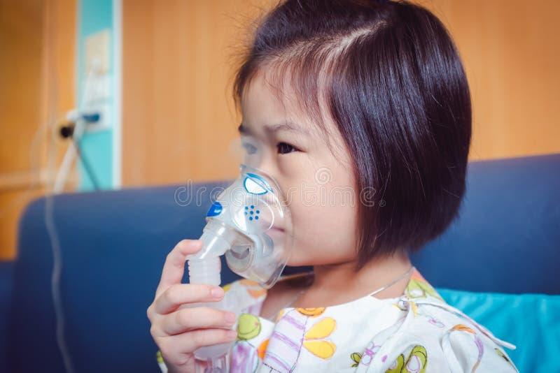 哀伤的亚裔孩子拿着哮喘的治疗的一台面具蒸气吸入器 库存图片