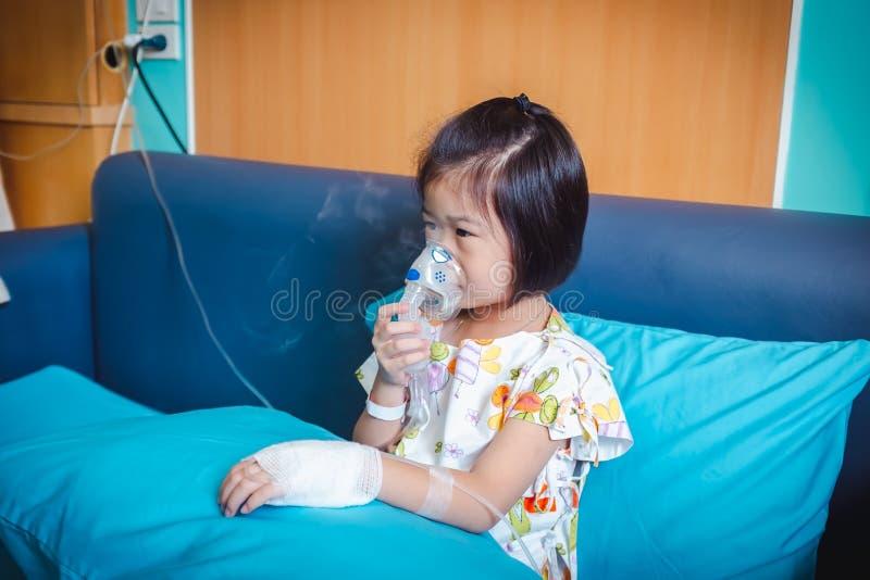 哀伤的亚裔孩子拿着哮喘的治疗的一台面具蒸气吸入器 免版税图库摄影