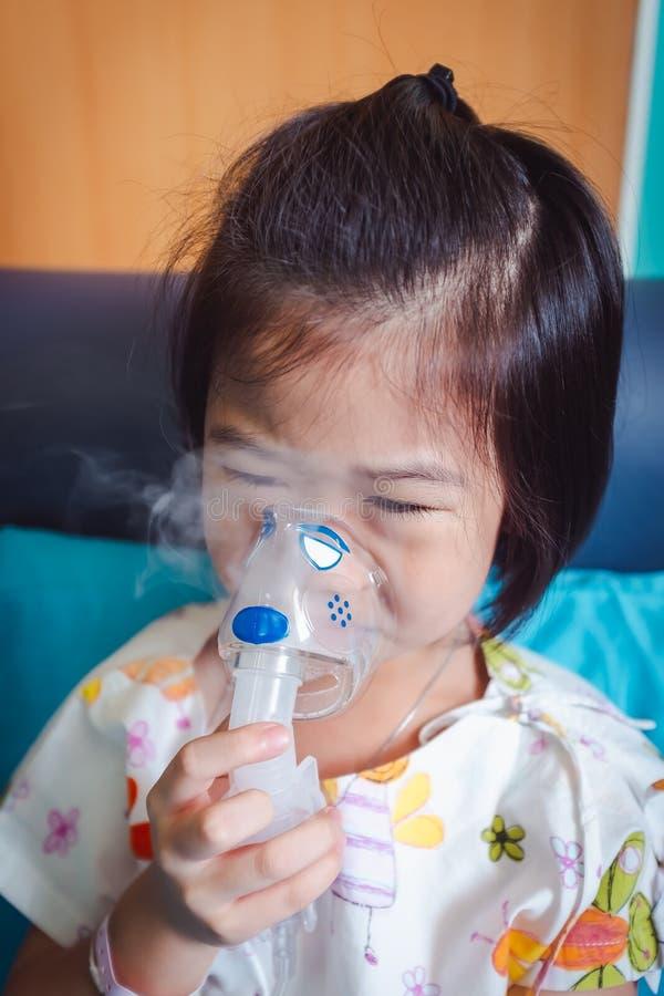 哀伤的亚裔孩子拿着哮喘的治疗的一台面具蒸气吸入器 免版税库存图片