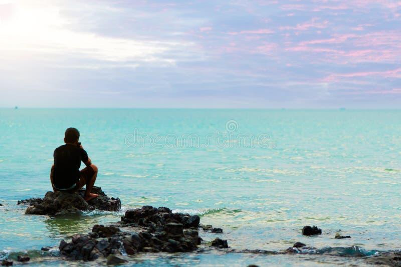 哀伤的人坐岩石在感觉的海偏僻和残破的hea 库存图片