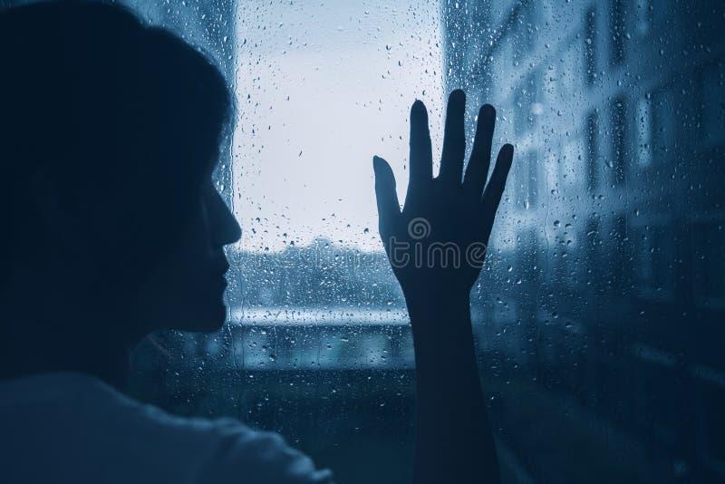 哀伤的偏僻的消沉心情妇女剪影接触玻璃窗雨天 免版税库存图片