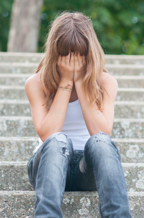 哀伤的十几岁的女孩单独坐台阶在夏天 免版税库存照片