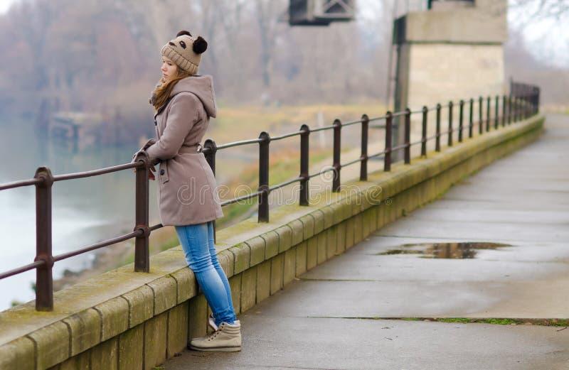 哀伤的十几岁的女孩常设外部在冷的冬日 免版税图库摄影