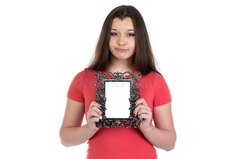哀伤的十几岁的女孩的图象有照片框架的 免版税库存照片