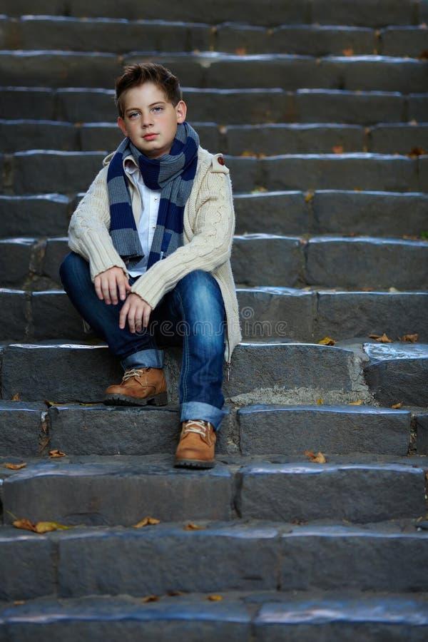 哀伤的十几岁的男孩坐室外石的台阶 库存图片