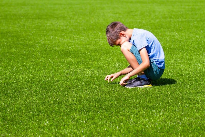 哀伤的单独男孩坐草户外 免版税库存图片