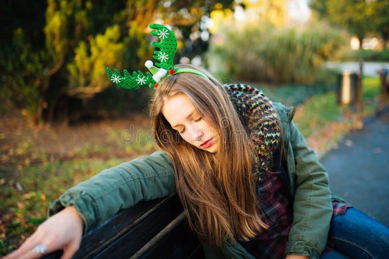 哀伤的可爱的女孩坐长凳 免版税图库摄影