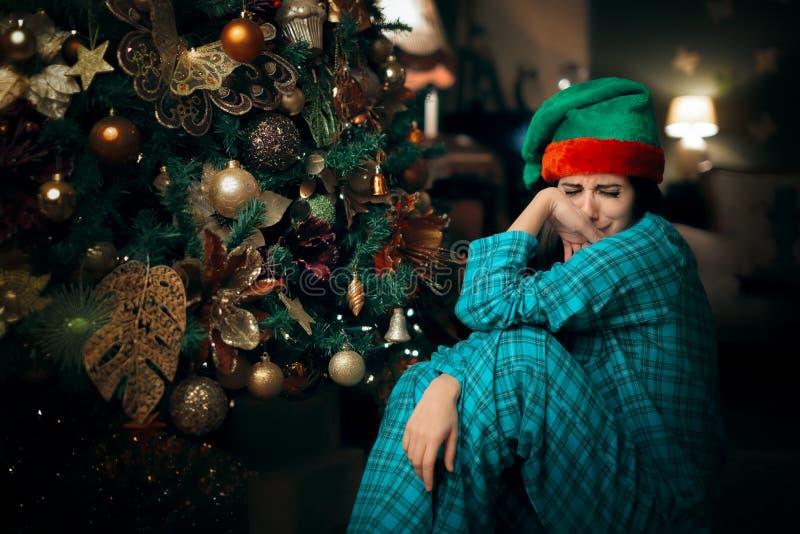 哀伤的哭泣在她的圣诞树旁边的翻倒孤独的女孩 免版税库存照片