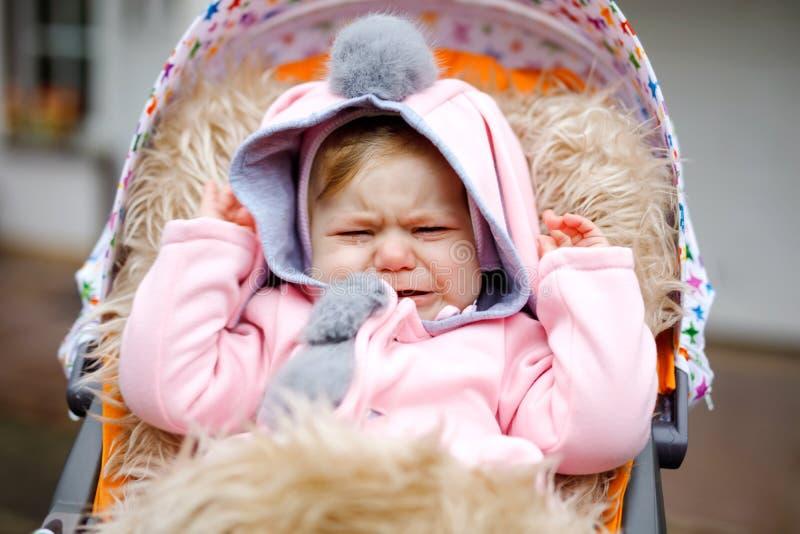 哀伤的哭泣的小美丽的女婴在摇篮车或婴儿推车坐秋天天 不快乐的疲乏和被用尽的孩子 免版税库存图片