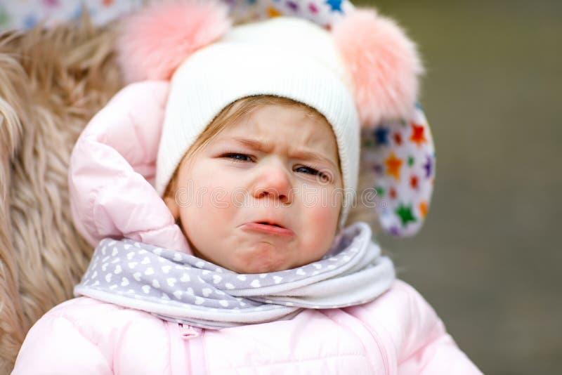 哀伤的哭泣的饥饿的女婴在摇篮车或婴儿推车坐冷的天 库存图片