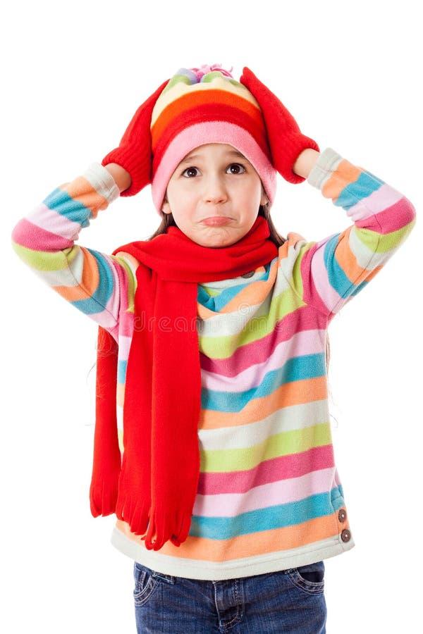 哀伤的女孩在冬天给采取他的头穿衣 免版税库存图片