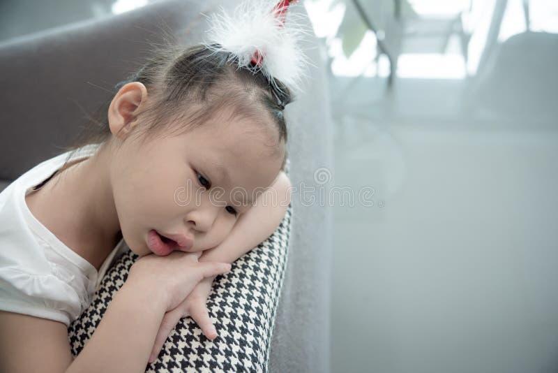 哀伤的女孩在家坐沙发 免版税库存图片