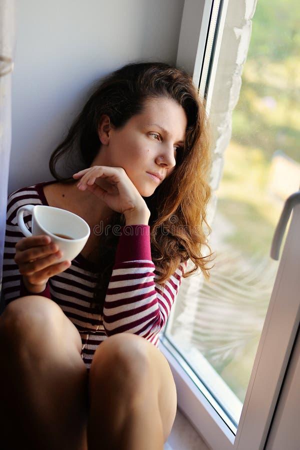 哀伤的女孩坐在与一杯茶的一个窗口,咖啡 库存照片