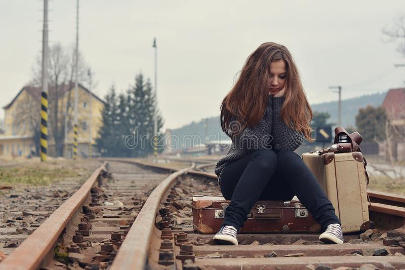 哀伤的女孩坐在路轨的老手提箱 免版税库存图片