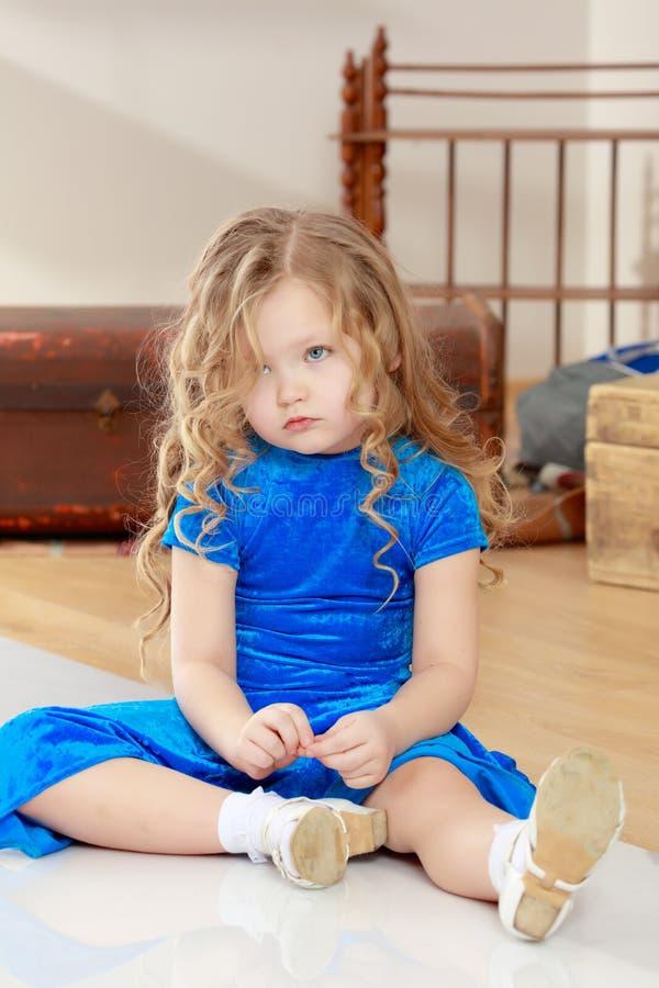 哀伤的女孩坐地板 免版税库存照片