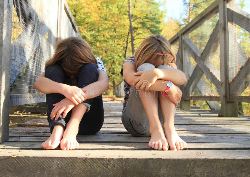 哀伤的女孩坐桥梁 免版税库存图片
