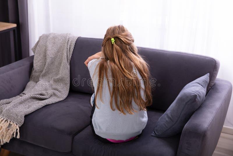 哀伤的女孩坐沙发 图库摄影