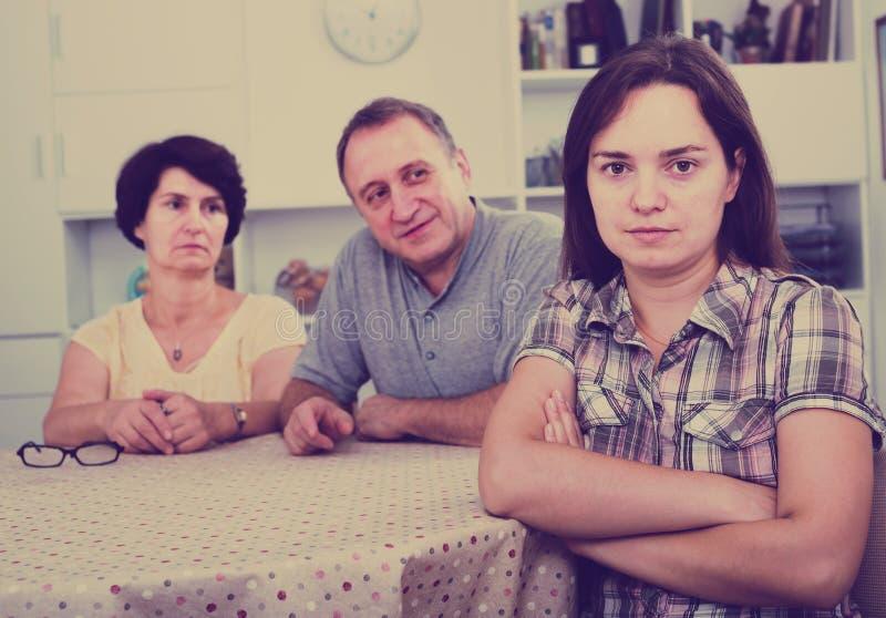 年轻哀伤的女孩由她的退休人员父母懊恼 免版税库存图片