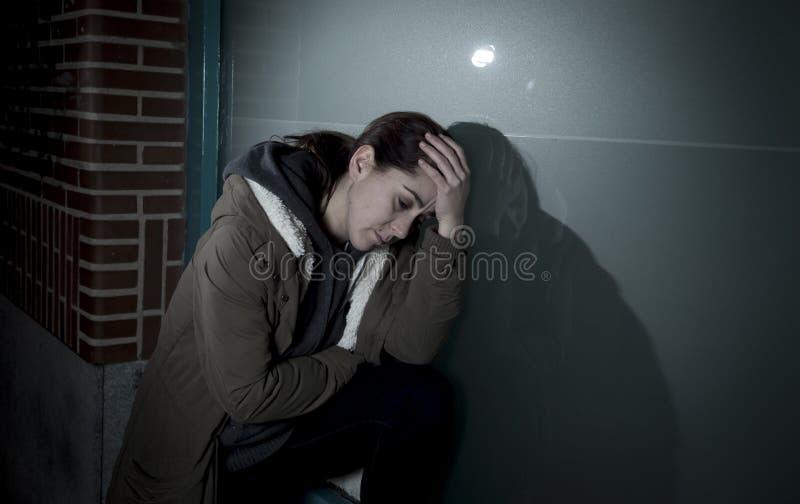 哀伤的妇女单独倾斜在哭泣在痛苦中的夜遭受的消沉的街道窗口 库存照片